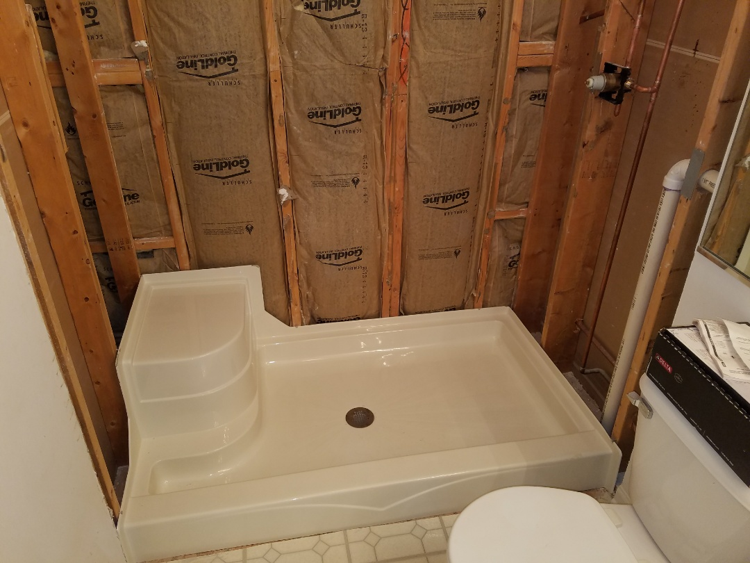 Install a new shower base and valve to start a bathroom remodel.