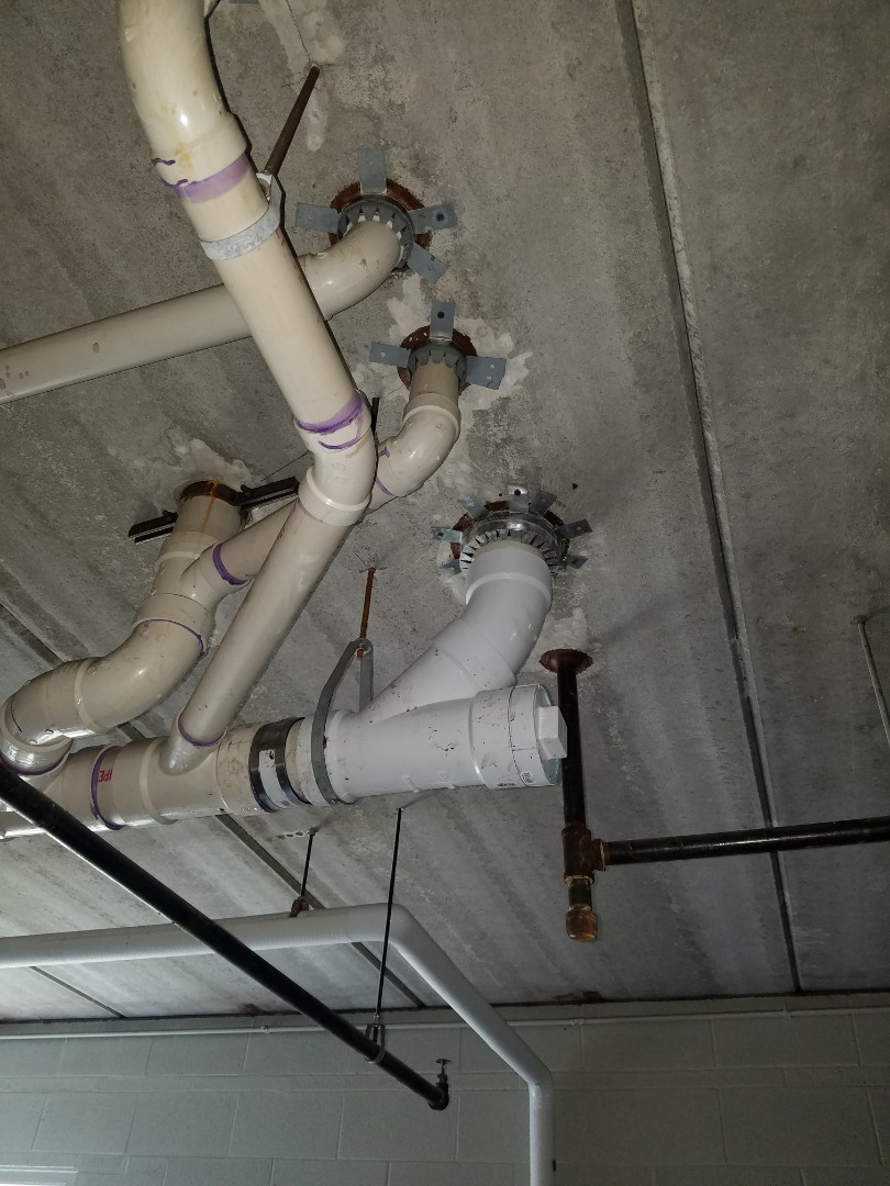 Repair a cracked drainage pipe leaking between floors of a condo building.
