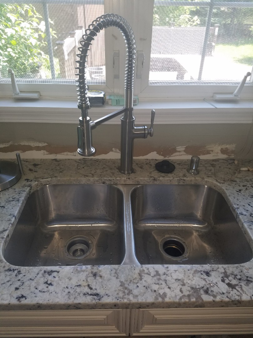 Install a new faucet and hook up drainage systems to complete a kitchen remodel.