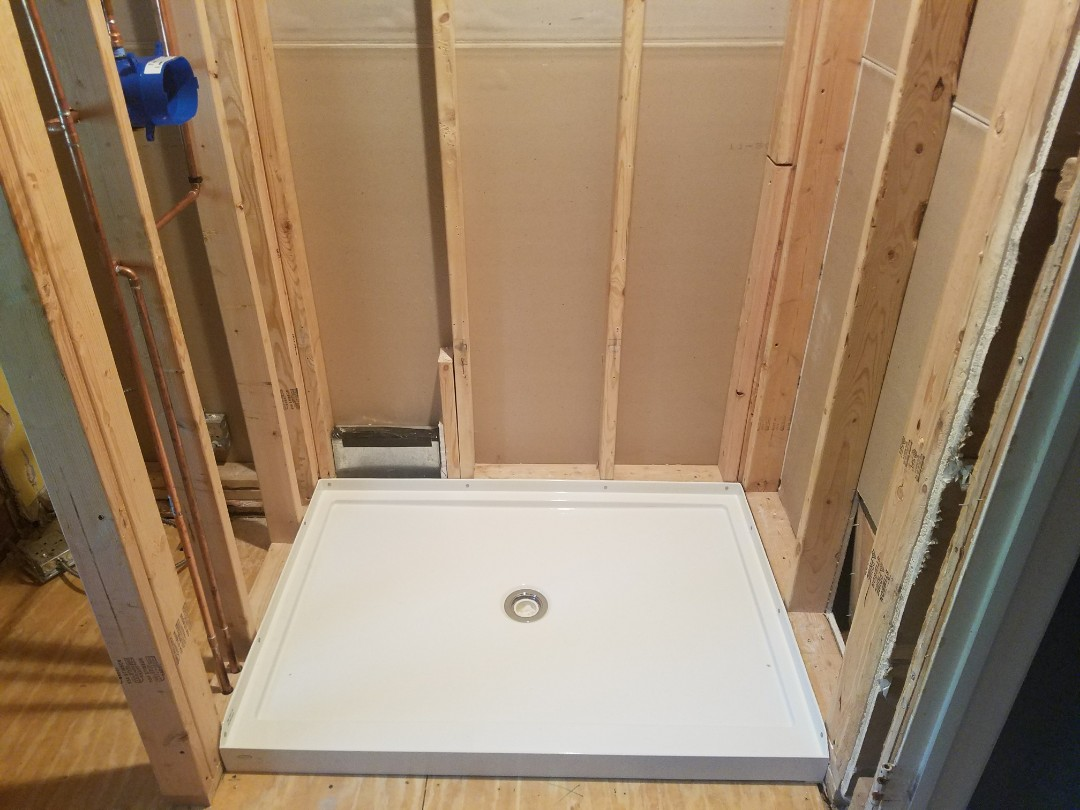 Complete the rough-in of a new shower valve and base for a bathroom renovation.