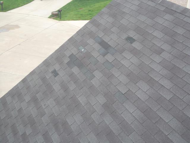 Eureka, MO - Inspecting roof with numerous shingles blown off