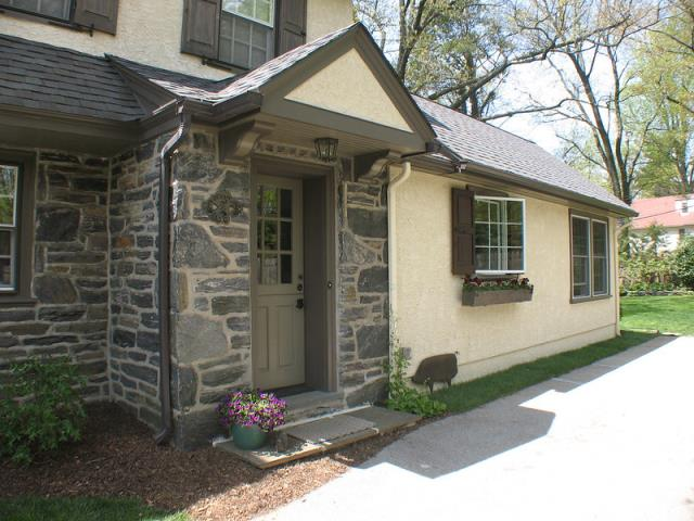 Wynnewood, PA - Dutch Colonial kitchen addition and whole house remodel in Wynnewood. Pictured is a new stone entrance portico with new Dutch door. The kitchen addition with stucco finish and planter box is on the right. A new family room and fireplace were part of this project for an interior designer owner and her family.