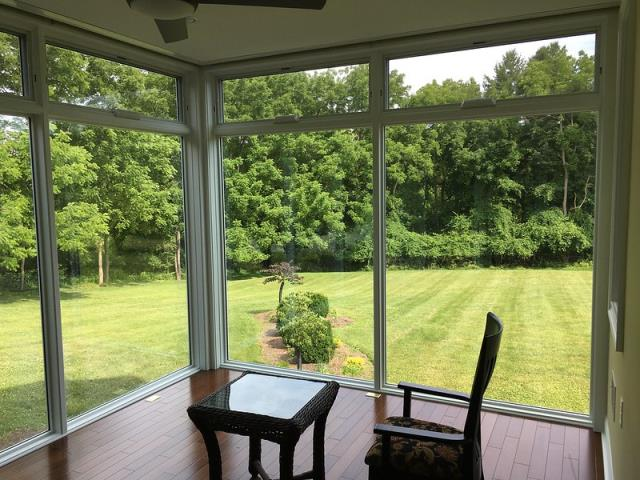 , PA - Sunroom / breakfast room conversion in Malvern, PA. The lines between outdoors and indoors are erased with the floor to ceiling Pella windows which include electrically operated transom awning windows at the top. Hidden inside the ceiling are electrically operated MechoShades providing privacy and shade at the touch of a button when wanted. The floors are beautiful Merpauh Java hardwood with inset brass plates for electrical outlets.