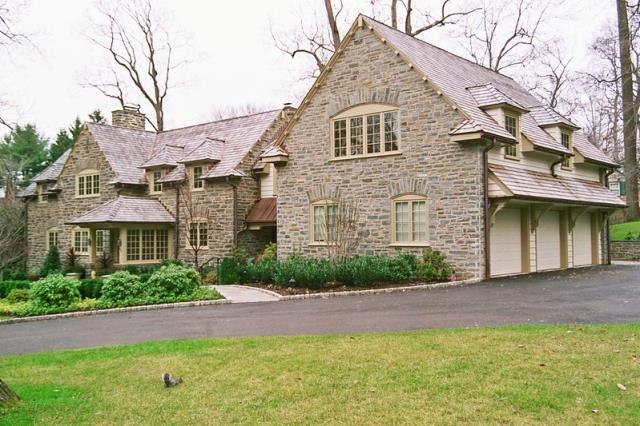 Bryn Mawr, PA - Interior and exterior renovations to this Bryn Mawr stone manor home. Photo shows new stone facade on garage, dentil moldings at roof line, new windows, copper roof portico, new pent roof over garage doors with corbels. Interior work includes a new kitchen, and a full basement remodel.