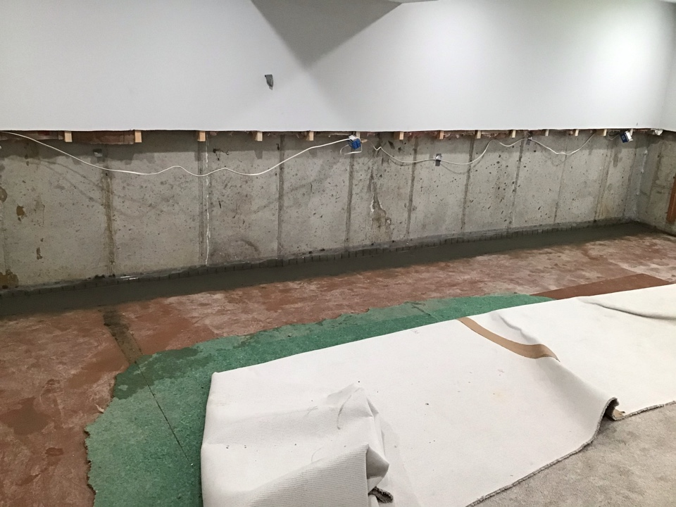 This finished basement was in need of a drain system after flooding.