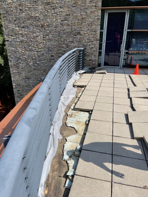 Roswell, GA - Roof Coating Repair - There are multiple leaks along the edge of the patio.  We will have to remove the pavers and the insulation board.  After cleaning the roof we will use flashing grade Unisil elastomeric along the entire edge.  We will then apply a 3 feet wide top coat of Unisil II, replace the insulation, and re-install the pavers.