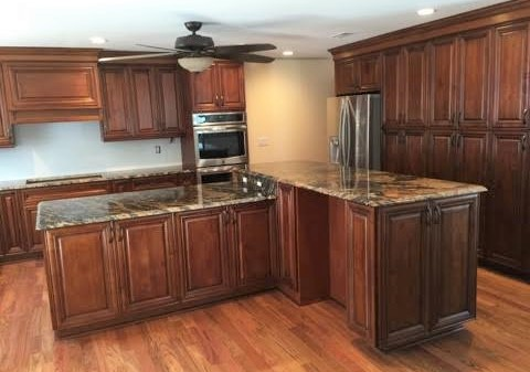 Williamsburg, VA - Take a look at this unique and massive island with seating on both sides of the bar height portion. I have to say that our coffee cabinets look great with the magma gold granite the home owner selected!