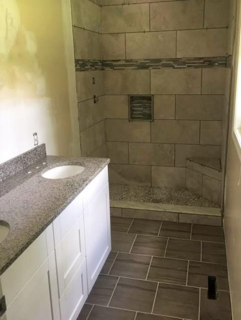 Ashland, VA - Our customer could not have picked a better match for her new bathroom! The New Caledonia granite and white shaker cabinets are perfect with the floor and shower tile she just had installed.