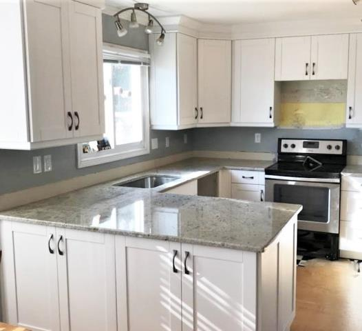 Mechanicsville, VA - The new larger peninsula we just installed for this whole kitchen remodel offers extra storage on the back along with more counter surface area. The handles the homeowner selected to accompany the white shaker cabinets and colonial white granite are perfect.
