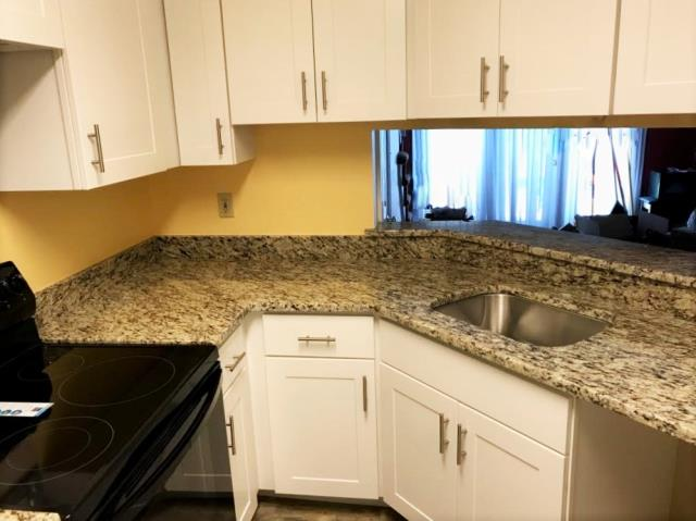 Richmond, VA - What a refreshing difference the Venetian ice granite and white shaker cabinets make from the original oak cabinets and cream laminate counter our client had before!