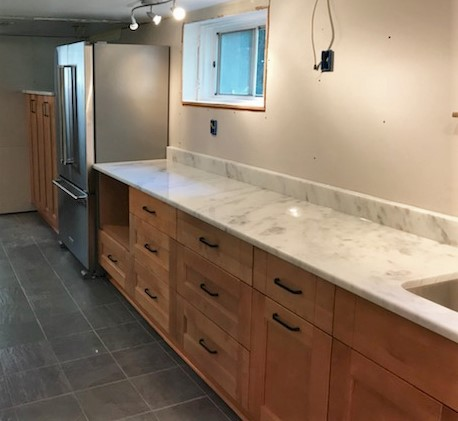 "Richmond, VA - Finished installing this unique and inviting ""English basement"" kitchen. We love the contrast between our cool Shadow Storm granite and gray slate floors with our warm natural maple cabinets and rustic handles. We're looking forward to seeing what backsplash and open shelves add to the space."