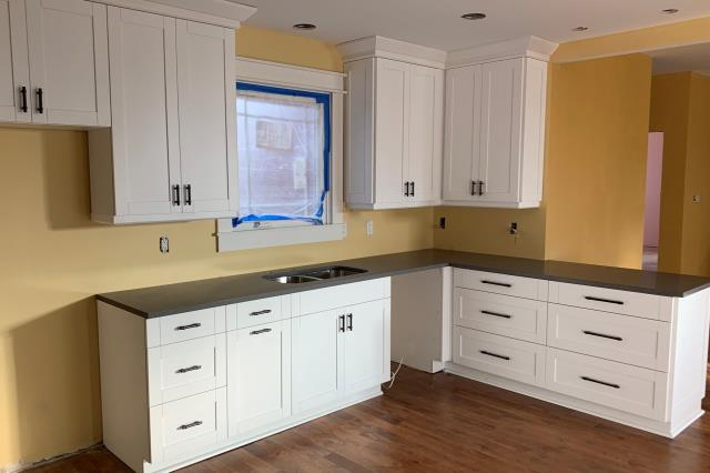 Richmond, VA - We love our white shaker cabinets with dark handles and our in-stock concrete gray quartz counter!