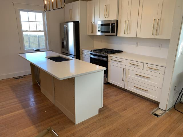 In-stock classical white quartz installed at $55/SF with the white shaker cabinets.