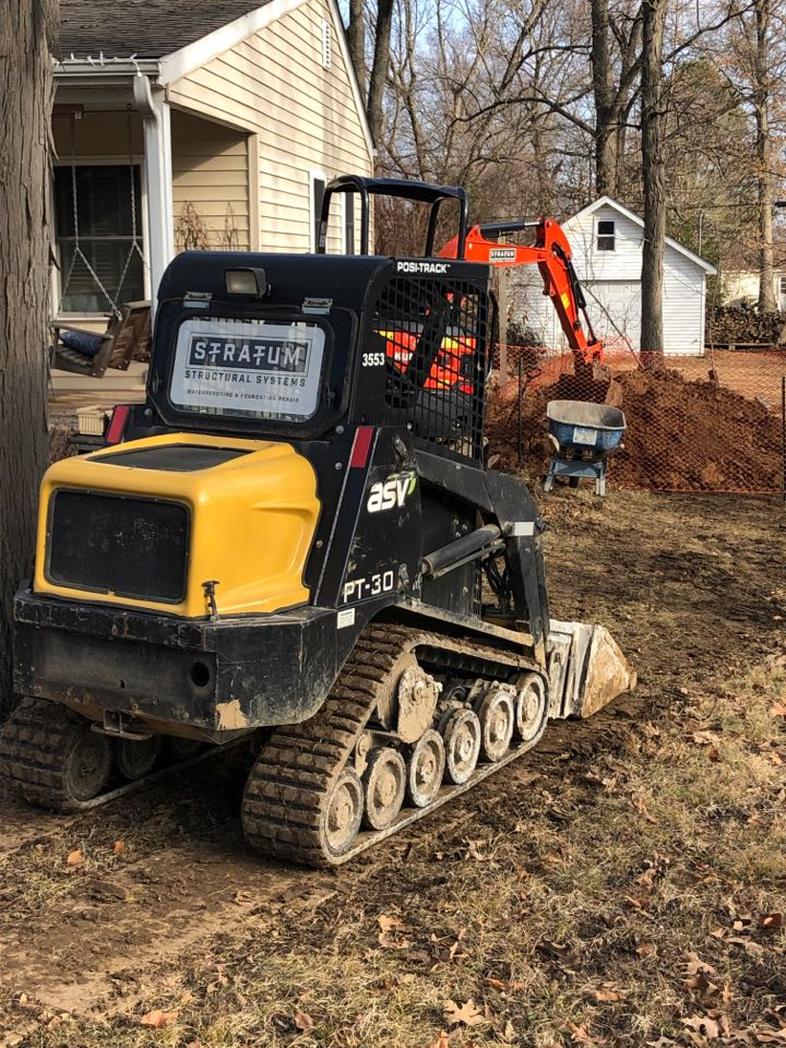Ballwin, MO - Day 1 of installing helical tiebacks anchors to straighten a foundation wall.    Tieback anchors are used to prevent bowing foundation walls from expanding clay soils.
