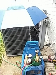 New Albany, MS - Keeping things dry while changing a suction accumulator on a outdoor heat pump for McGee Insurance in New Albany,Mississippi.