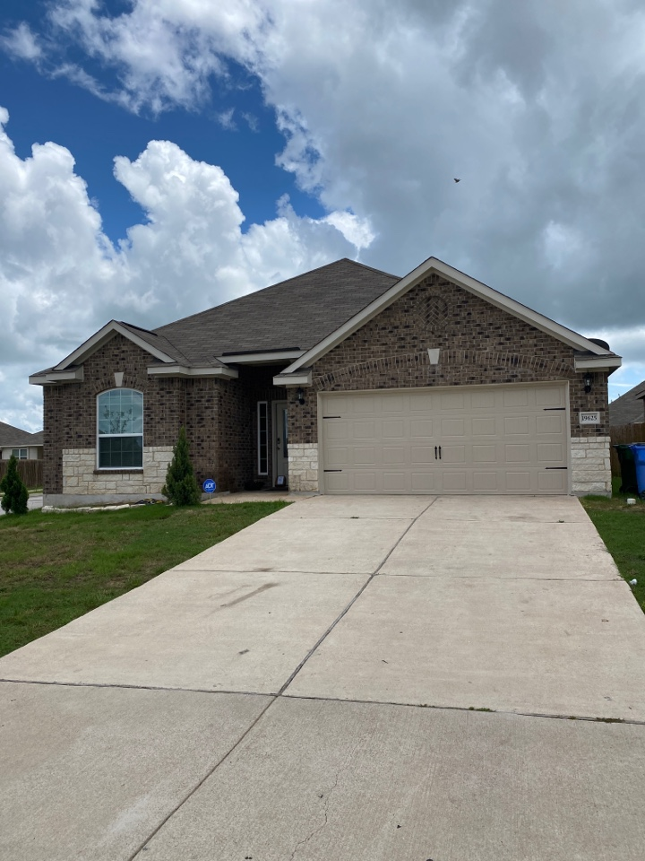 Manor, TX - Measuring the house for gutters and downspouts