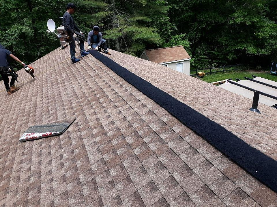 Voluntown, CT - The crew installing GAF Seal-a-ridge ridge caps over GAF Cobra ridge vent  along the peak of the new GAF Shakewood Timberline HD roof system.