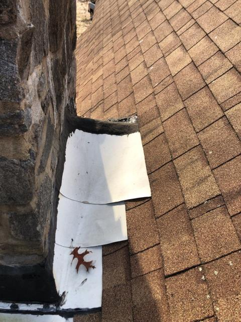 Richmond, RI - Interesting way to flash a chimney? All new lead flashing will need to be installed and a cricket to shed water away from behind chimney on this roof in richmond RI. and a new GAF Timberline HD shingle installed.