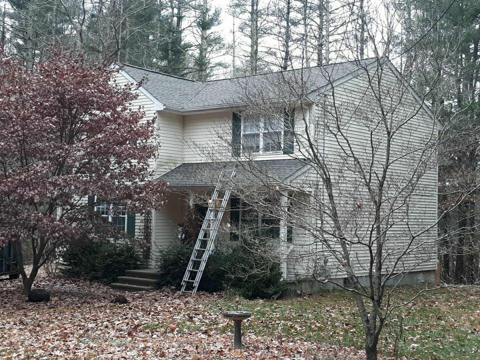 Hopkinton, RI - A tree bounced off of today's home resulting in a damaged roof and side wall. Our crew just finished installing this new GAF Timberline HD Weathered Wood roofing shingle system, with matching GAF Seal-A-Ridge ridge caps over GAF Snow Country ridge vent. The damaged sheathing was replaced before the GAF Weather Watch and GAF FeltBuster underlayment was laid, and the crew even took the extra time to replace the side wall sheathing, the house wrap, and the damaged vinyl siding, soffit and fascia.