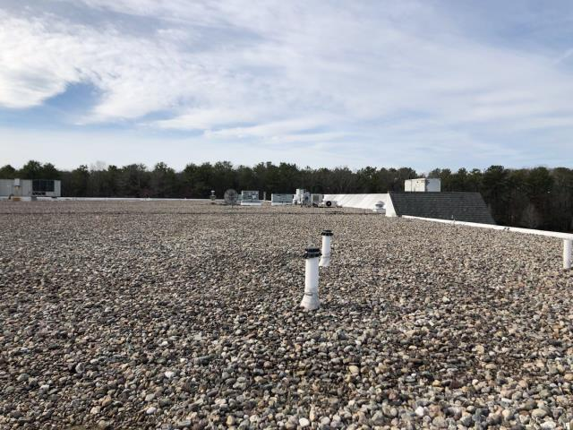 New London, CT - This ballasted roof system is in need of replacement. It can be difficult to find roof leaks with a ballasted roof, the loose stones block us from a visual inspection. This roof will have all the stone removed and then a new TPO roof system will be installed.
