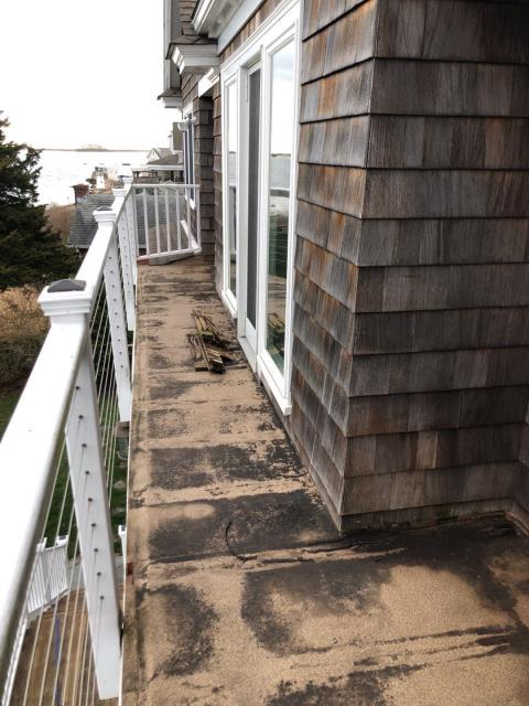 Charlestown, RI - Inspecting a flat roof that was leaking in Charlestown RI. Old deck boards were removed so we can access roofing membrane. Will need to remove old roofing and some siding to install new EPDM roofing membrane properly.