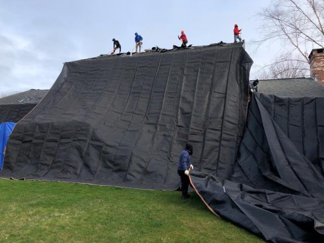 South Kingstown, RI - Crew is installing Large heavy duty canvas tarps to protect this property from damage during this full roof replacement project in South Kingstown RI. New Roof NO mess! The clean up and removal of debris and often over looked by contractors. We will be recycling the old asphalt roof shingles so they can be used in new roads.