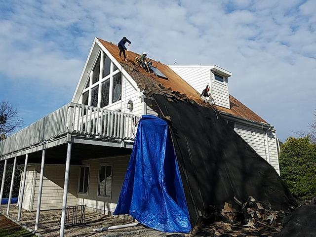 Charlestown, RI - Here the crew is removing the old layer of old roof shingles. It is always better to remove old shingles then to go over! Crew has set up heavy duty tarps to protect this property from damage, New Roof no mess in Charlestown RI