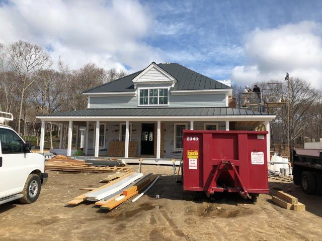 South Kingstown, RI - Metal roof installation is almost complete in South Kingstown RI. Drexel standing seam metal being installed. Crew is working the chimney flashing with the mason today.