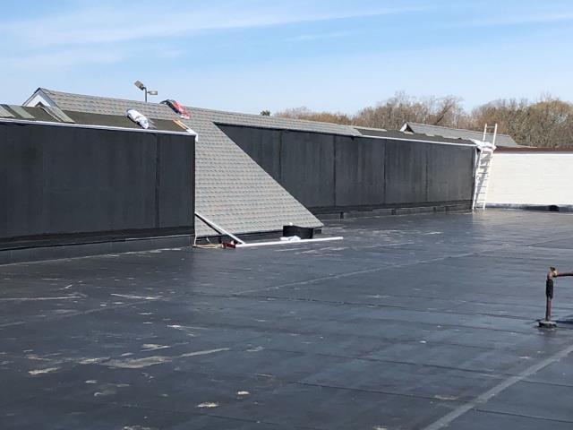 North Kingstown, RI - Making progress on this commercial roofing project in North Kingstown RI. Here the crew has replaced the shingles and plywood on the sloped areas Using GAF Timberline HDZ shngles. Color is williamsburg slate.EPDM rubber membrane repairs and some sections will replaced.