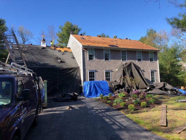 Charlestown, RI - Roofing crew has most of the old worn out roof shingles removed by 8;30! This full roof replacement using GAF timberline shingles will have a Golden Pledge Warranty!
