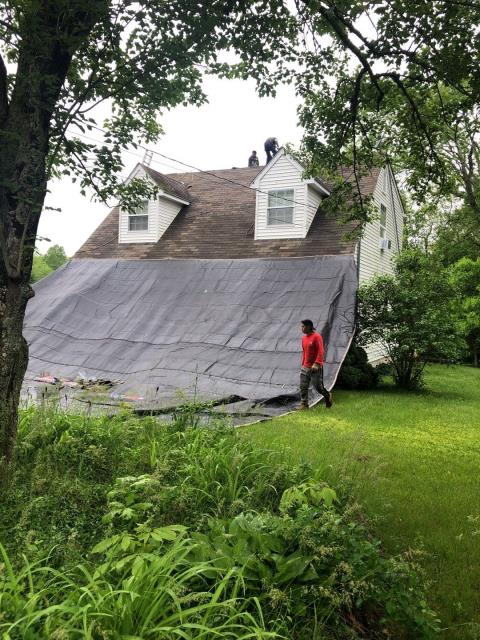 Griswold, CT - Roofing crew is setting up tarps to protect property on this roof replacement project in Griswold ct. Old shingles are being removed and recycled. New GAF timberline shingles will be installed.