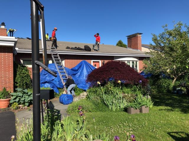 New London, CT - Crew is on site setting up tarps to protect this home during the roof replacement process. New GAF Timberline shingles to be installed after removing old worn out roof shingles.