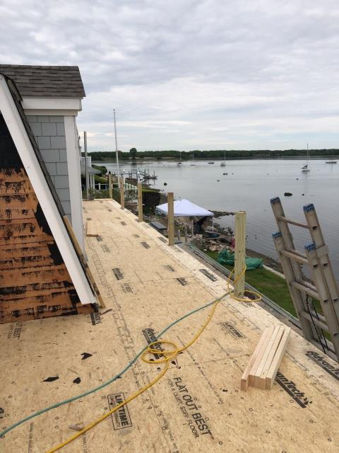 North Kingstown, RI - Measuring for a new EPDM rubber membrane roof to be installed under a new deck. Also will be installing new roof shingles to match existing roof. New wood cedar shake siding. North Kingstown RI.