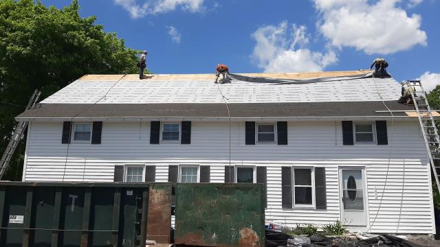 Richmond, RI - Roofing crew has completed the removal of the old shingles and old chimneys.Now we are installing the GAF Ice & Water and the GAF synthetic paper. Next the GAF Timberline roof shingles will be installed.