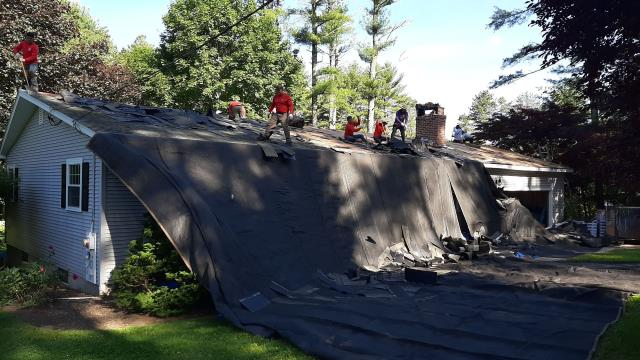 Hopkinton, RI - Roofing crew always sets up heavy duty tarps to protect the property. This roof is getting replaced with new GAF Timberline shingles.