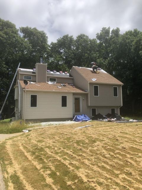 Ledyard, CT - Crew is hard at work installing the new GAF Timberline roof shingles on this house in Ledyard CT. Full roof replacement. Color shakewood.