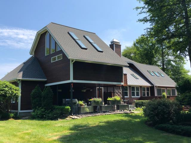 Narragansett, RI - This Roof replacement is now 100 percent complete! GAF Timberline shingles were used for the asphalt roof replacement, Drexel Standing seam Metal roof was used for the Metal accent roofs. All new Velux skylights were installed.