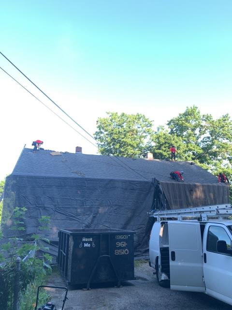 Plainfield, CT - Our roofers in Plainfield CT are setting up large heavy duty tarps to protect the property. Roofers are removing the old roof shingles before installing the new new GAF roof system