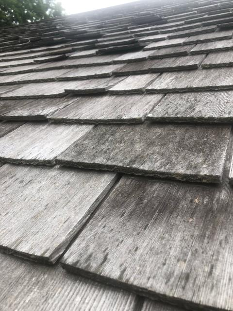 Stonington, CT - Inspecting a wood roof in Deep River CT. These shingles are curling and showing signs of wear. Improper nailing allows the shingles to curl. We recommend removing the old wood shakes and installing new Cedar 5/8 tapersawn roof shingles. Or a New GAF Timberline ULTRA HD shingle.