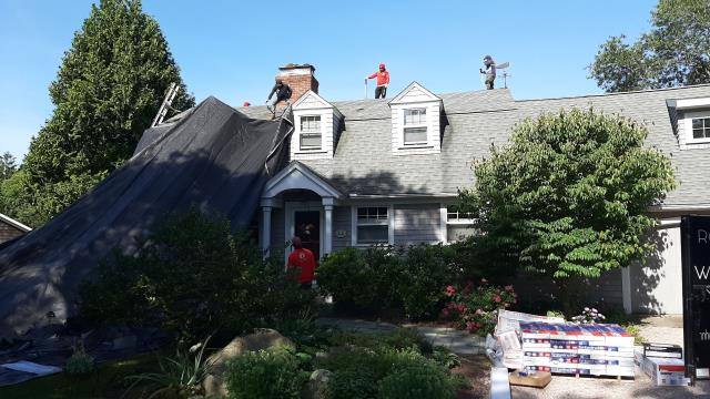 Charlestown, RI - Here our roofing crew in Charlestown RI is setting up heavy duty tarps to protect this house and flowers during the roof replacement process. New GAF Timberline shingles will be installed