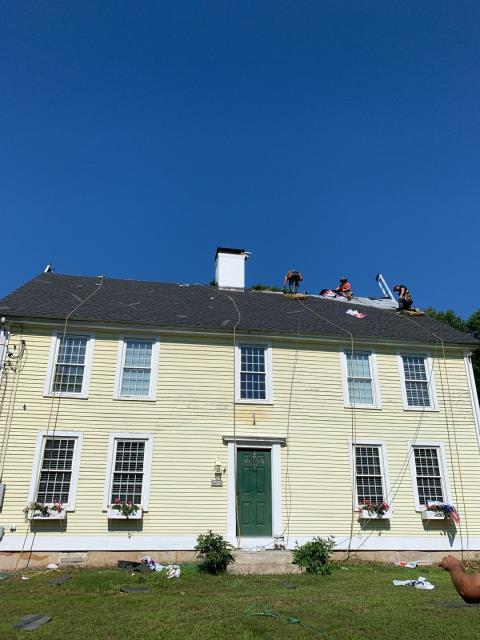 Griswold, CT - This colonial style home in Griswold CT is getting a new GAF Timberline Roof shingle installed! New lead flashing on chimney done by Mason. All new vinyl replacement windows and new vinyl siding will be getting done soon. New seamless gutters with gutter guards will be completed after siding.