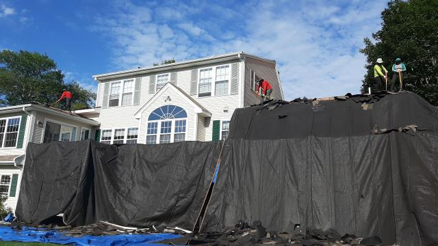 Narragansett, RI - Our roofers in Narragansett RI are setting up heavy duty tarps to protect the house and plants from damage during the process of removing the old roof shingles prior to the new roof getting installed. Rolling magnets will be run all day to collect the nails.