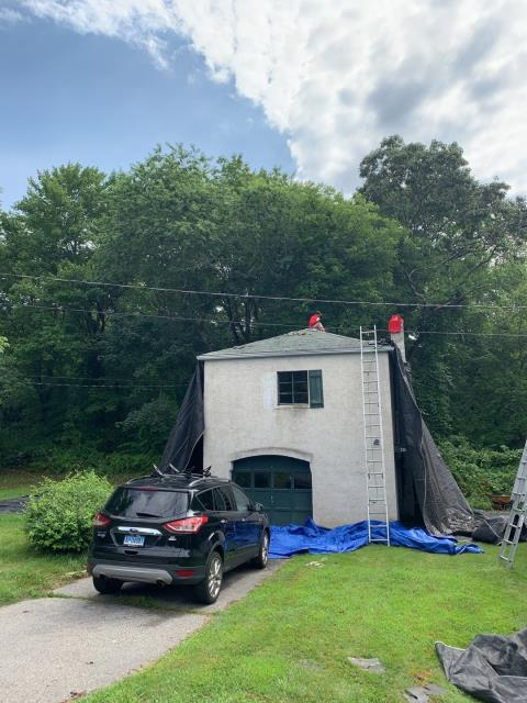 Groton, CT - Our roofers in Groton Ct are setting up protective tarps to make sure debris stays away from this detached garage and flowers! Rolling magnets are used to collect the nails. A new GAF Roof system Will be installed