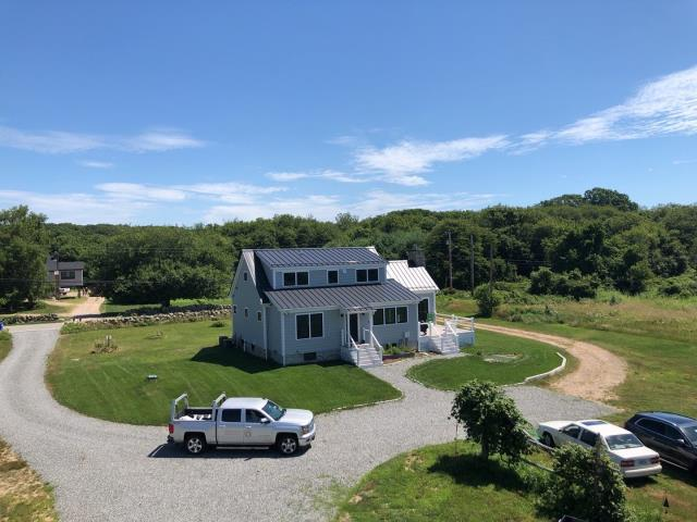 Charlestown, RI - View from the Barn roof looking back at a great looking standing seam metal roof! We will be replacing the barn roof with new GAF Timberline HDZ roof shingles.