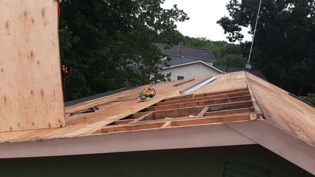 Westerly, RI - Roofing crew in Westerly RI is replacing damaged plywood on this roof during the roof replacement. All sheathing is inspected before installing the new GAF roof system