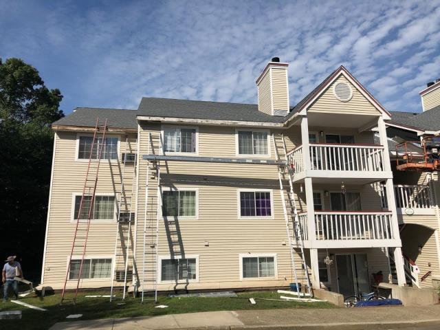 Jupiter Point, CT - This apartment building in Groton CT has already had the roof replaced using GAF Timberline Shingles. These roofs had damage from the high winds. Now our siding crew is installing new aluminum trim and vinyl soffit