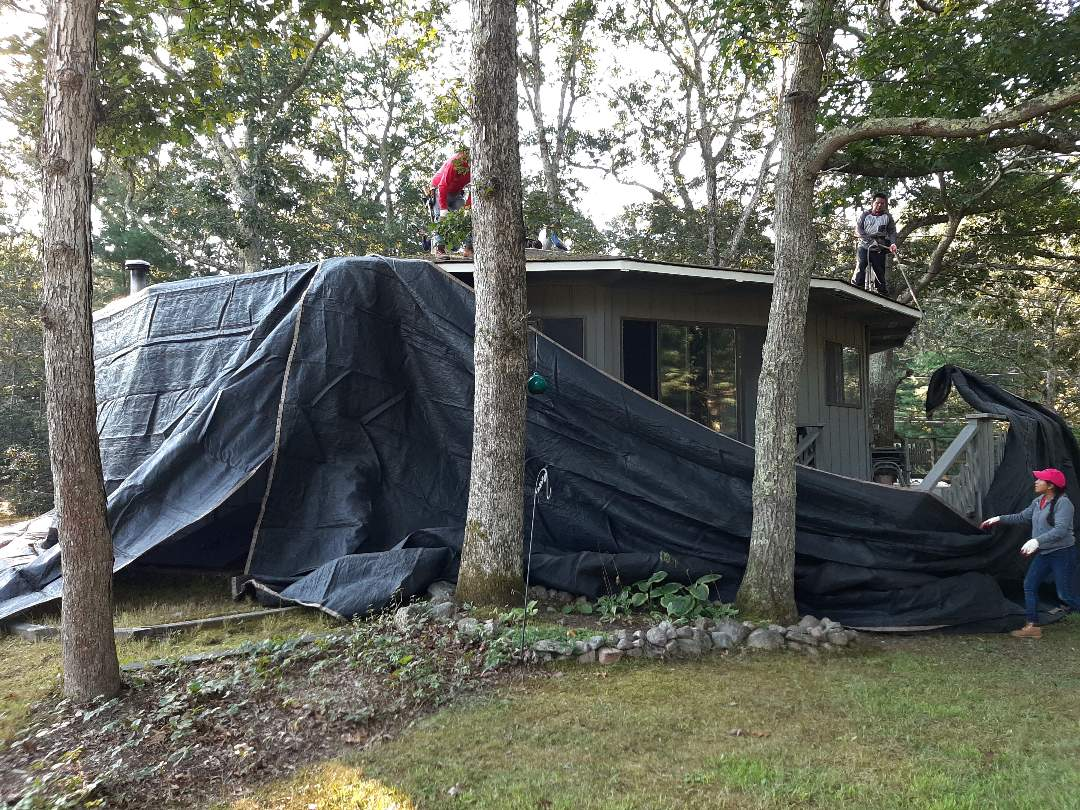 Charlestown, RI - Out in Charlestown today. We will be replacing roof with a new GAF roof system. Crew is setting up tarps to protect house and plants before starting to strip shingles.