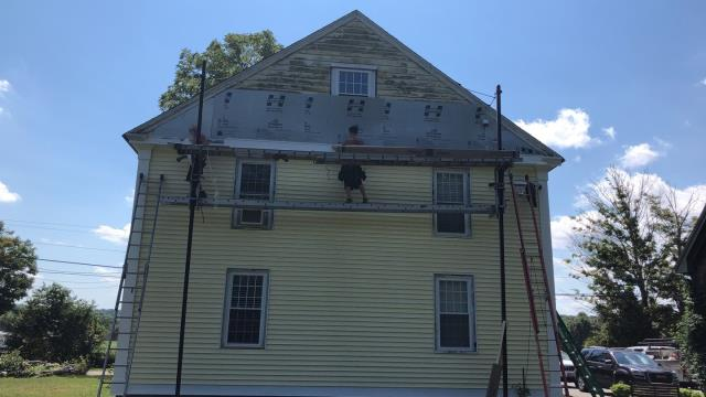 Griswold, CT - One of our siding crews is hard at work today installing the new vinyl siding on this house in griswold ct. No more painting will be needed on this historic farm house!