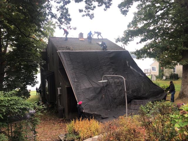 Voluntown, CT - Roofing crew in Voluntown Ct is setting up tarps to protect this property in on Beach Pond. A full roof replacement will be completed today using all GAF Roofing accessories and new GAF Timberline HDZ shingles.