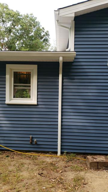 Hopkinton, RI - New white seamless gutters and gutter guards installed after we completed the new vinyl siding installation on this house in Hope Valley RI.